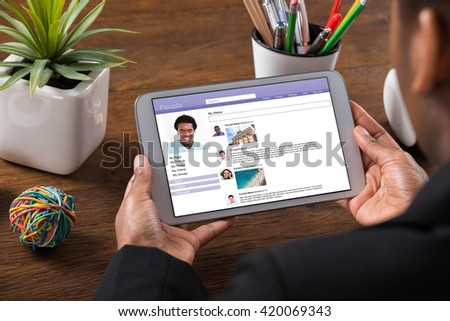 Close-up Of Young Businesswoman Chatting On Social Networking Site Using Digital Tablet