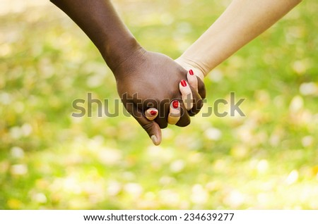 Close up on a mixed race couple holding hands in the park