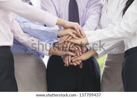 Close up on arm and hands of group of business people with hands on top of each other