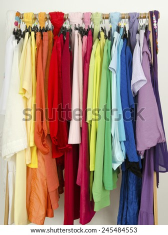 Close up on color coordinated clothes on hangers in a store. All colors clothes hanging on a rack nicely arranged.