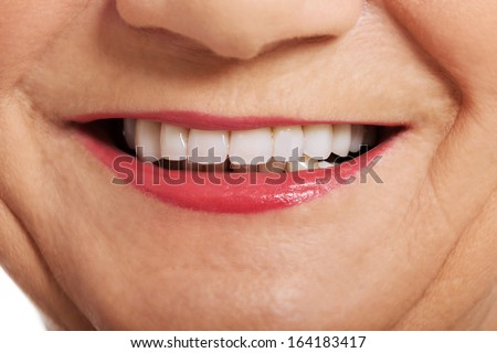 Close up on ol woman's perfect smile, teeth. Over white.