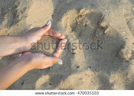 Close up on woman hands holding sand. Summer beach holiday vacation concept