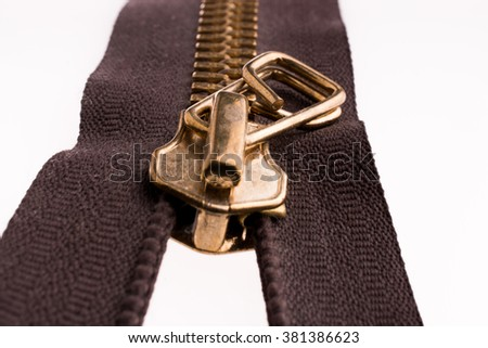 Close up or macro of a  brown zipper and a little model man on white background