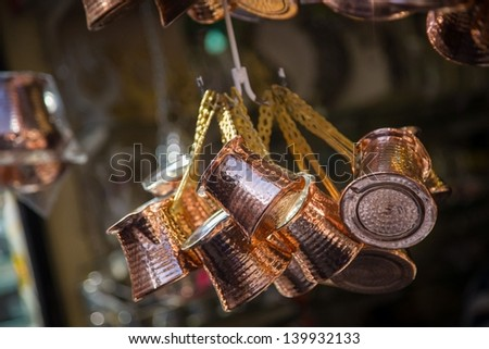 Close up photo of a bunch of copper coffee pots hanged up in a market in Istanbul