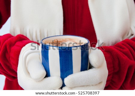 Close up photo of a woman in warm gloves holding cup of hot chocolate with marshmallows at winter. selective focus