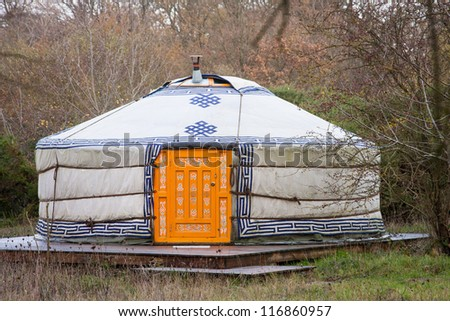 Close-up photo of one white yurt with blue simbols and big closed well-decorated orange door in the forest on an autumn day