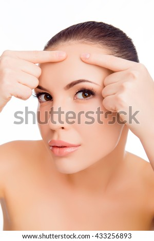Close up photo of pretty woman crushing acne on her brow