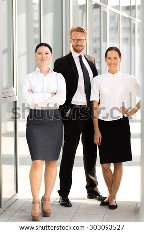 Close-up picture of business people in full length. Tall man in glasses posing with his hands in pockets, businesswomen smiling.