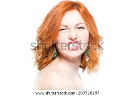 Close-up portrait of a beautiful redhead woman, grin. Isolated on white background. Facial expression and emotions.