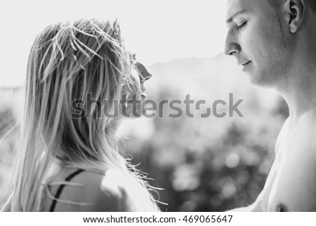 Close-up portrait of a beautiful young kissing couple in bed at home
