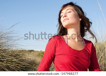 Close up portrait of a beautiful young woman breathing fresh air while sitting on a beach sand dunes with her eyes closed, leaning her head back and enjoying the breeze on vacation.