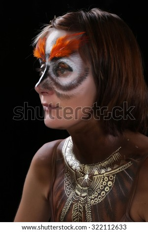 close-up portrait of a girl in a mask of an owl, body art studio on a black background