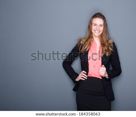 Close up portrait of a happy young business woman smiling and holding black suit jacket on gray background