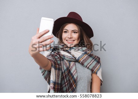 Close up portrait of a smiling cute woman in hat taking selfie with smartphone over gray background