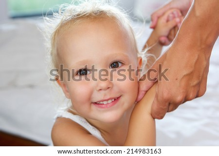 Close up portrait of a smiling little girl holding mother hands