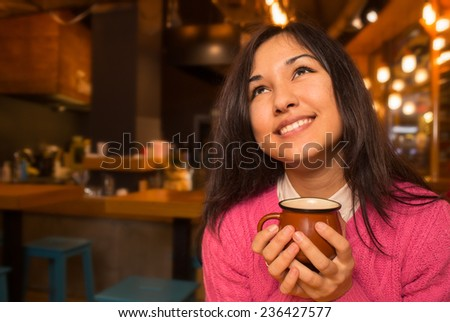 Close-up portrait of a young lovely woman with a latte cup in hands  in cafe. Cheerful young asian lady at the restaurant