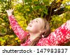 Close up portrait of a young teenage girl standing in a forest during the autumn season, surrounded by changing color leaves with her arms outstretched up and head back, outdoors. - stock photo