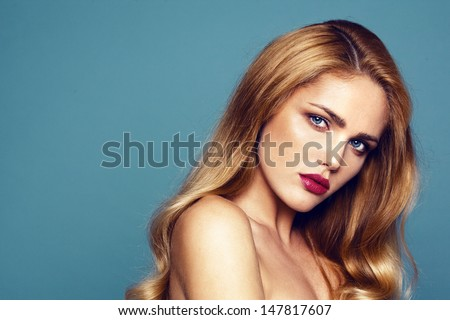 Close-up portrait of beautiful model with bright lips. Shooted on dark turquoise background