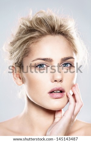 close-up portrait of beautiful model with natural make-up, shooted on blue background