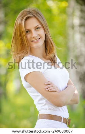 close-up portrait of beautiful young blond woman in white blouse at park holding her neck