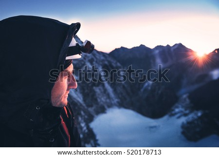 Close up portrait of climber. Climber reaches the summit of mountain peak. Climbing and mountaineering sport concept