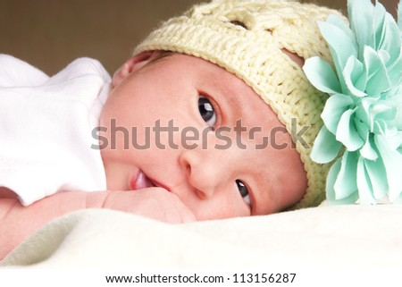 Close-up portrait of cute newborn baby girl in funny hat, studio shot