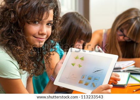 Close up portrait of cute young student holding tablet with homework.