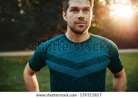 Close up portrait of fit young man in sportswear standing outdoors. Confident fitness male model in park.