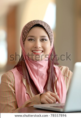 Close-up portrait of pretty young Asian Muslim woman at coffee shop while surfing internet