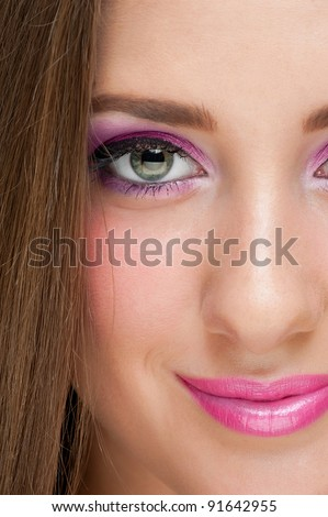 Close-up portrait of pretty young woman with bright violet make-up
