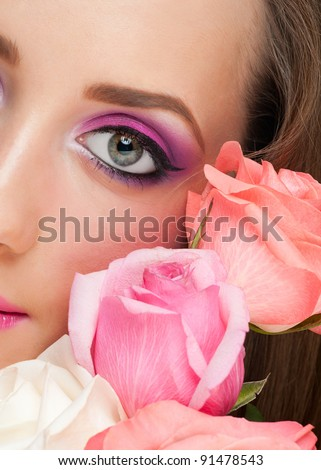 Close-up portrait of sensual beautiful woman with roses and stylish bright make-up