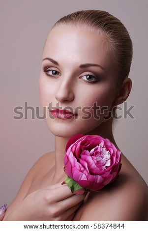 Close-up portrait of sexy beautiful young woman with pink flower