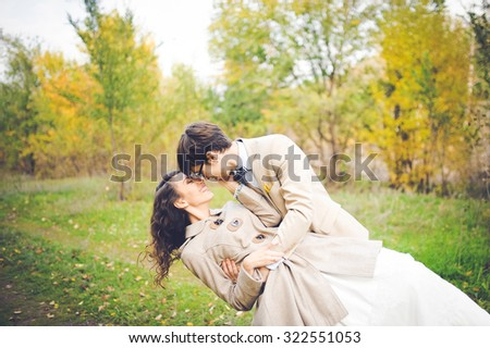 close-up portrait of wedding couples in love hipsters bride in a white dress with flowers and groom in a suit with glasses and bow tie smiling  posing touching embrace on a background of autumn forest