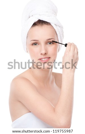 Close-up portrait of young beautiful woman with brush for make-up. Eyelashes zone