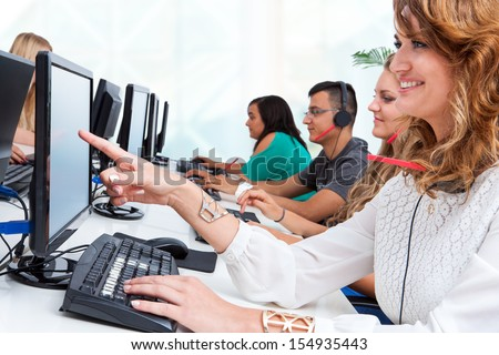 Close up portrait of young female student pointing at blank computer screen in office.