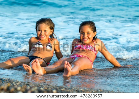 Close up portrait of young girls enjoying summer holidays together on beach.