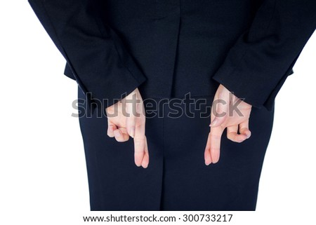 Close up pretty businesswoman with finger crossed against a white wall