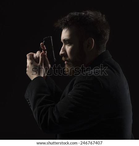 Close up Serious Young Man Wearing Black Long Sleeve Shirt Holding Small Gun While Facing Left. Isolated on Black Background