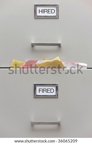 Close up shot of a filing cabinet with labels reading hired and fired.  The 'fired' drawer is very full.  Vertically framed shot.