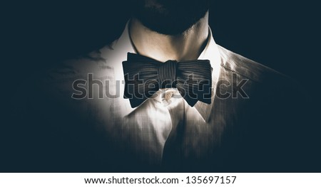 Close-up shot of a model man wearing classy bow tie, getting ready for a party, dinner or wedding