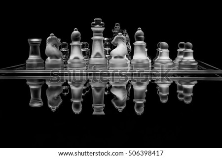 Close-up shot of glass chess set with reflection