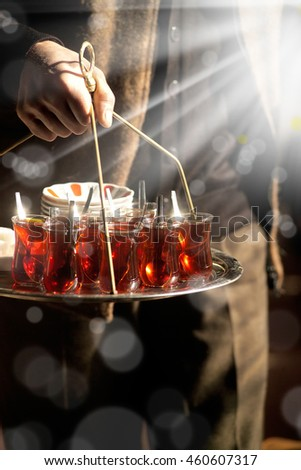 Close up shot of man holding full tea tray.