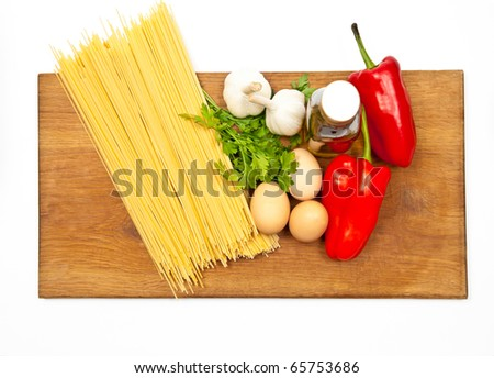 Close-up shot of spaghetti and vegetables on wooden board. Studio shot