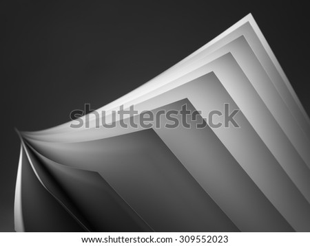 Close up shot of white paper fanned out on a black background with a shallow depth of field and copy space for the designer.