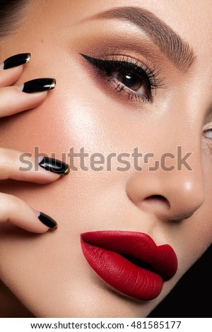 Close-up shot of woman lips with red lipstick. Beautiful perfect lips. Sexy mouth close up. Beautiful wide smile of young fresh woman with full lips. Isolated over black background