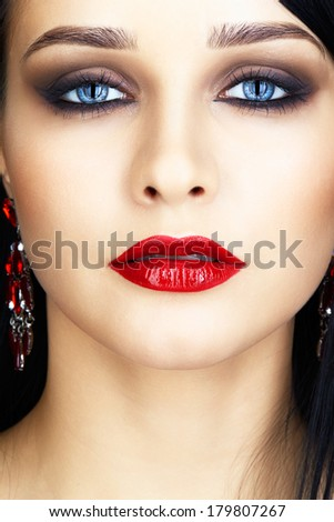 Close-up shot of young brunette woman face with evening makeup