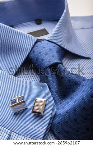 Close up shots of blue striped man's shirt with blue dotted tie and cuff links