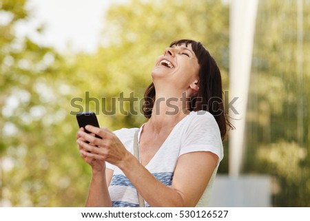 Close up side portrait of laughing older woman holding smart phone outside
