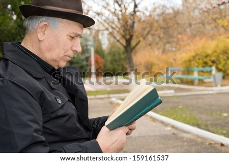Close up side view portrait of an elderly gentleman in an overcoat and hat reading his book outdoors in the autumn sun and enjoying the peace of the public park