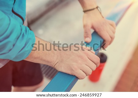 close up sportsman's hands holding railing